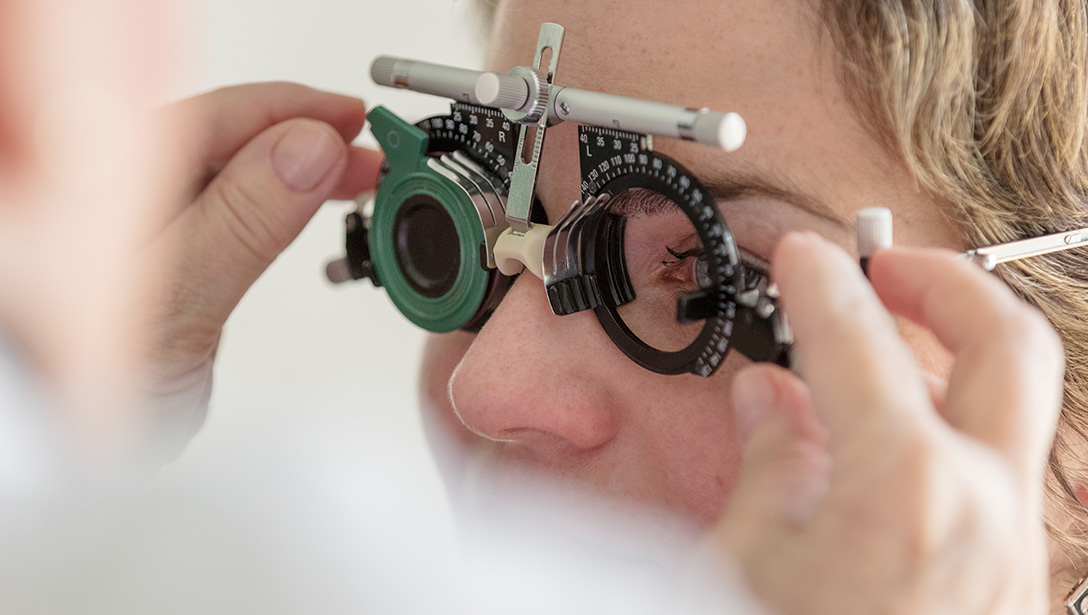 Eye doctor administering eye exam with eye exam tool.