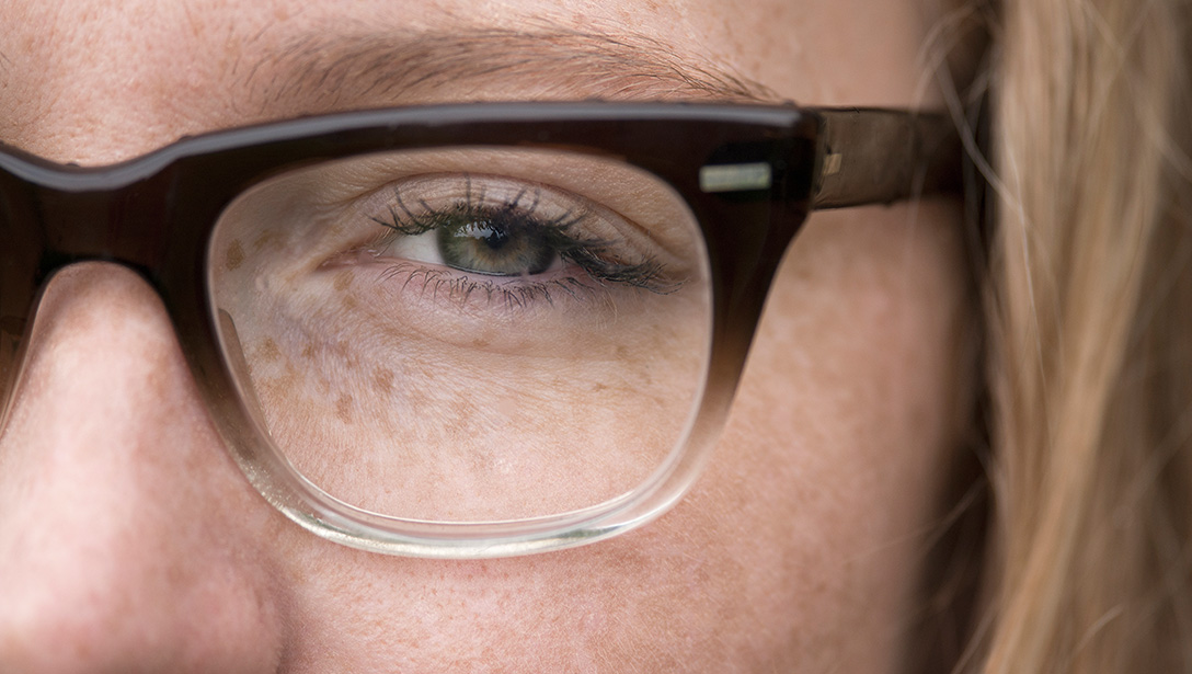 Close up of women's left eye while wearing glasses.